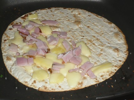 Put ham and cheese on the tortilla